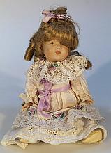 An early 20th Century German porcelain doll, with fixed hair in early part worked clothing, marks be
