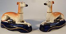 A pair of 19th Century Staffordshire greyhound inkwells, of recumbent form, polychrome decorated in