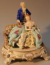 An R K Dresden figure group, of a gentleman standing before a lady and puppy, polychrome decorated w