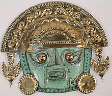 A 20th Century brass painted metal Inca style wall hanging, of mask form with raised geometric decor