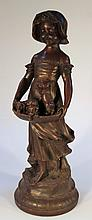 A Spelter figure, of a girl, standing in bonnet and flowing robes, holding a basket of puppies on a