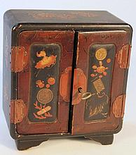 An early 20th Century Japanese black lacquered jewellery box, in the form of a cabinet, decorated wi