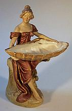 A late 19th Century Royal Dux figure, of a lady seated holding a large shell, polychrome decorated i