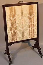 An Edwardian mahogany articulated fire screen, with adjustable central section centred by a brass ha