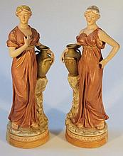 A pair of late 19th Century Royal Dux figures, each formed as female water carriers beside urns on n