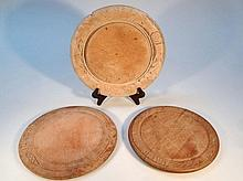 An early 20th Century wooden bread board, of circular form, with a carved outer banding, 27.5cm dia.