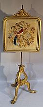 A 19th Century giltwood and metal pole screen, the cylindrical stem fronted by a carved panel headed