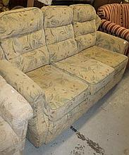 A three seater settee, in floral material predominantly in green and fawn, of modern construction, 9