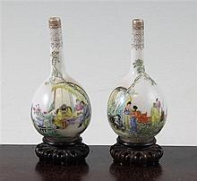A pair of Chinese famille rose eggshell porcelain miniature bottle vases, Qianlong seal mark, Republic period, 9.8cm., rosewood stands,