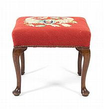 A George II Walnut and Needlepoint Footstool, Height 18 x width 18 1/2 x depth 19 inches.