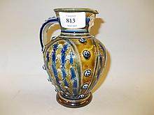 Doulton Lambeth stoneware jug decorated with mottled brown and blue glazes with mask head spout, 5.75ins high