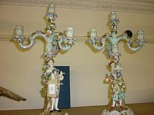 Pair of late 19th Century Continental porcelain floral encrusted figural candelabra, blue pitchfork marks to base (very slight losses)