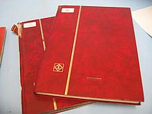 Two red stock books containing a collection of various World stamps