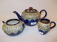 Royal Doulton three piece stoneware tea set with floral relief moulded decoration (small chip to spout)