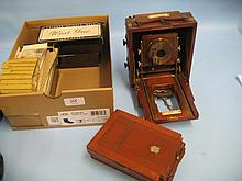 Quantity of glass stereoscopic slides together with a small mahogany and brass mounted plate camera with four plate holders