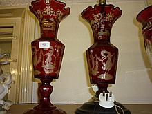 19th Century Bohemian red flash faceted baluster form vase on circular foot with all-over etched decoration of figures etc together with another matching (converted to a table lamp)