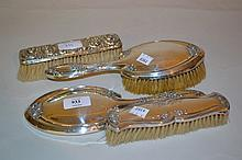Sheffield silver floral embossed Art Nouveau style three piece dressing table set and another silver backed floral embossed brush