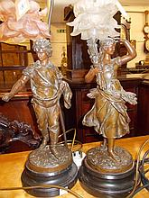 Pair of 19th Century dark patinated spelter figures of a man and woman adapted for use as table lamps with pink tinted glass shades
