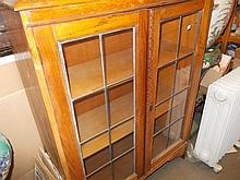 1930's Oak bookcase with two lead glazed doors raised on bracket supports