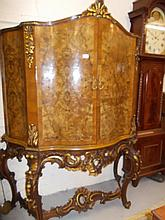 Large continental burr walnut serpentine fronted two door cocktail cabinet, raised on a heavily carved C-scroll and giltwood stand with stretchers