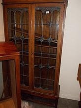 Early 20th Century oak bookcase with leaded glass doors on an associated base