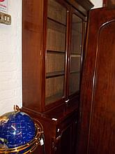 Victorian mahogany bookcase with moulded cornice above two glazed doors, an ogee drawer and two panelled doors above a plinth
