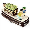 A Chinese Republic carved and coloured ivory group of children pulling a cart of corn on a rosewood and silver inlaid stand,