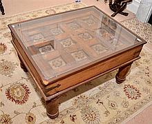 AN INDONESIAN COFFEE TABLE. THE GLASS TOP ENCLOSING ANTIQUE CARVED TIMBER PANEL