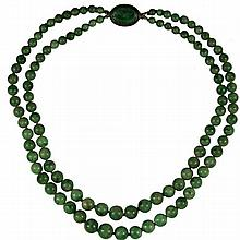 A VINTAGE DOUBLE STRAND JADE BEAD NECKLACE; 2 graduated stands of 4.3 - 9.2mm round beads of light opaque mottled green to oval silve..