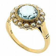 A 9CT GOLD TOPAZ AND SEED PEARL CLUSTER RING; centre set with a round cut light blue topaz of approx. 2.30ct surrounded by 14 seed p...