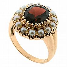 A 9CT ROSE GOLD GARNET AND PEARL CLUSTER RING; set with oval cut garnet of approx 3.12ct and 14 seed pearls. Size N 1/2