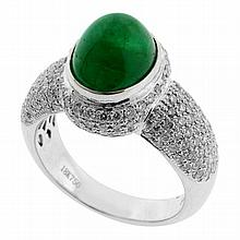 AN EMERALD AND DIAMOND RING; rub set in 18ct white gold with a cabochon cut emerald of approx 4ct to gallery and half round shoulder...