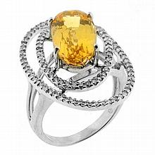 A GOLDEN TOPAZ AND DIAMOND DRESS RING; four claw set in 18ct white gold with an oval cut golden topaz of approx 5.98ct with 2 offset...