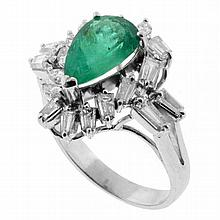 AN EMERALD AND DIAMOND RING; claw set in 18ct white gold with a pear shape medium green emerald of approx 2.30ct sounded by eight ma...