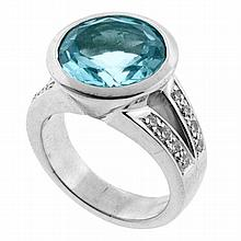 A TOPAZ AND DIAMOND RING; rub set in 18ct white gold with a round cut aquamarine of light blue colour approx 7.40ct (slight abrasion...