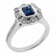 AN 18CT WHITE GOLD SAPPHIRE AND DIAMOND RING; centre rub set with and emerald cut sapphire approx 0.84ct surrounded by 16 round bril...