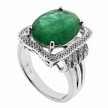 AN EMERALD AND DIAMOND RING; four claw set in 18ct white gold with an oval cut emerald of approx 3.70ct (few tiny chips) in decorati...
