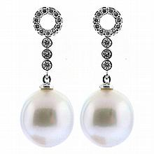 A PAIR OF SOUTH SEA PEARL AND DIAMOND EARRINGS; each a 11.4mm round white South Sea pearl of good lustre suspended by a line of 3 di...