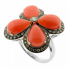 A CORAL AND DIAMOND RING; quatrefoil mount set with four cabochon pear shape corals surrounded by 53 round brilliant cut diamonds in...