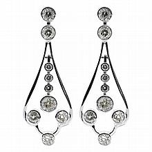 A PAIR OF 18CT WHITE GOLD DIAMOND DROP EARRINGS; each 2 rub set old European cut diamonds suspending a line drop of 4 old European c...