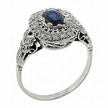 AN 18CT WHITE GOLD SAPPHIRE AND DIAMOND RING; centre set with an oval cut dark blue sapphire of approx 0.70ct with some abasions and...