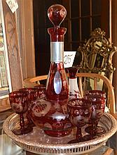 Seven-piece Bohemian cranberry overlay glass liquor set; a stoppered decanter and six liquors, etched and cut to clear glass decorat...