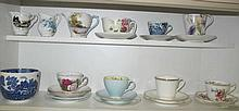 Two shelves of vintage porcelain trios and jugs