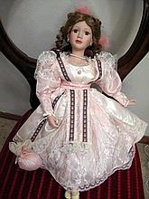 Vintage porcelain doll in pink dress measures 48cm