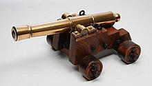 A MODEL OF AN OLD BRASS CANON mounted on a wooden