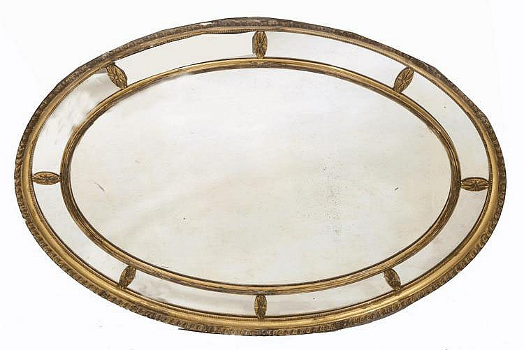 A 19TH CENTURY GILT MIRROR of oval form with
