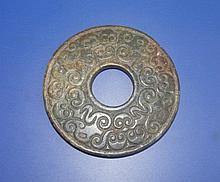 An archaistic Chinese carved jade Bi disc, of mottled green/brown colour, 3.4