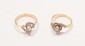 Ensemble de deux bagues en or jaune, chacune ornée d'un petit diamant dans un enroulement d'or gris diamanté.       Poids : 5,6 g.      An ensemble of two diamond and 18K gold rings.