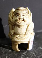 Un petit okimono en ivoire figurant un homme grimaçant