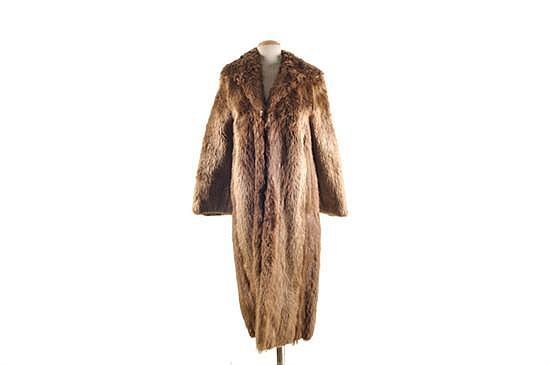 Abrigo largo. Elaborado en piel de racoon. Talla mediana. Presenta detalles de uso y el forro interior manchado.